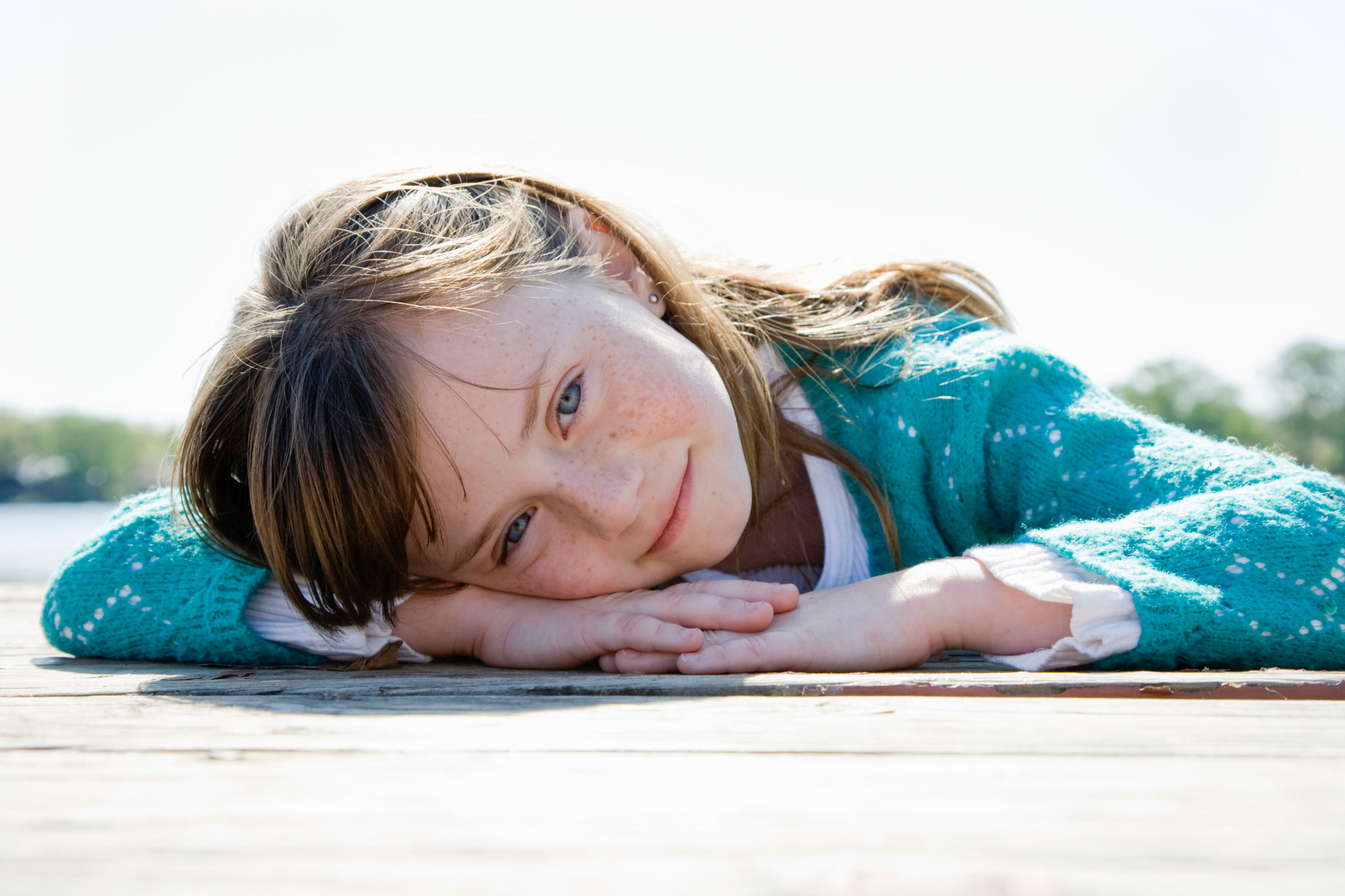 Girl (6-7), lying down resting head in arms on wooden deck, portrait